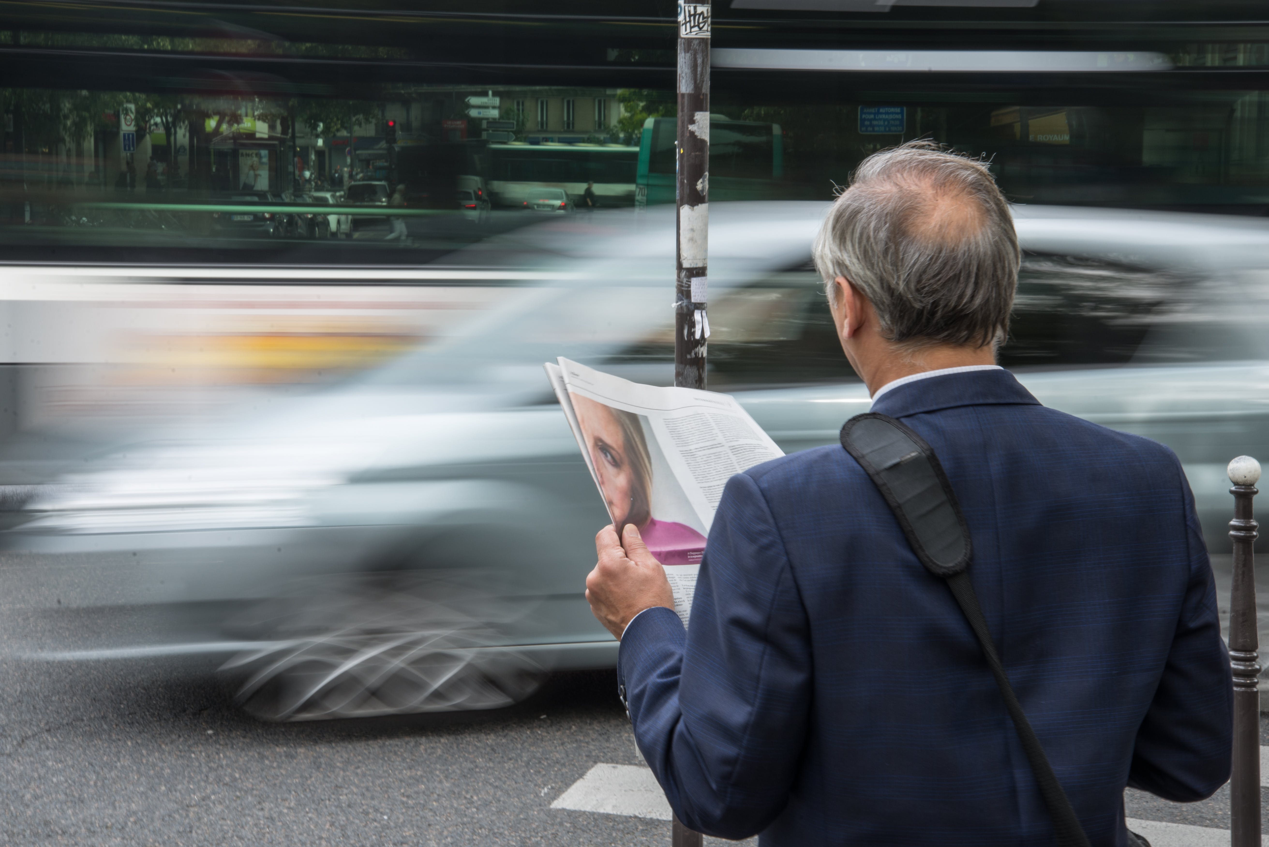 Man Wearing Blue Suit Jacket Holding Newspaper in Front Vehicle on Concrete Road