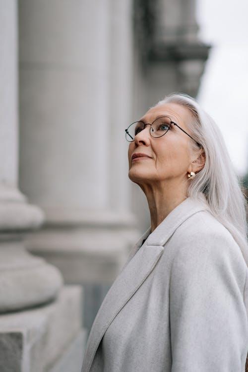 Woman in Gray Coat Wearing Black Framed Eyeglasses