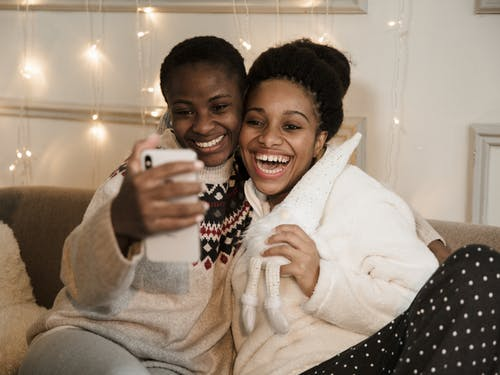 Women Smiling Holding A Mobile Phone