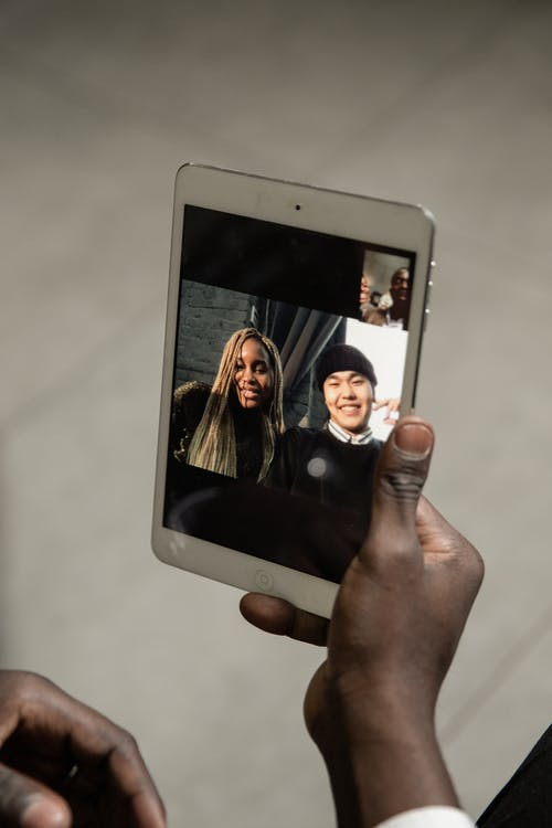 Person Holding White Ipad Displaying Man And Woman