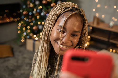 Woman Smiling Holding Red Smartphone