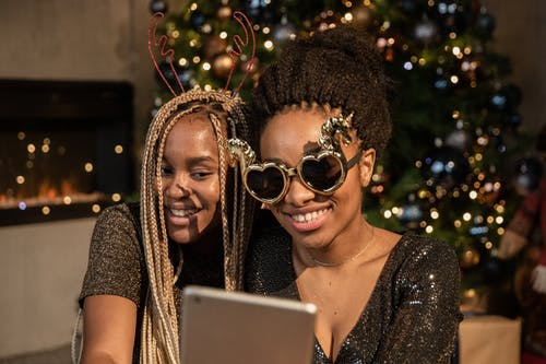 Two Women Smiling While Holding An Ipad