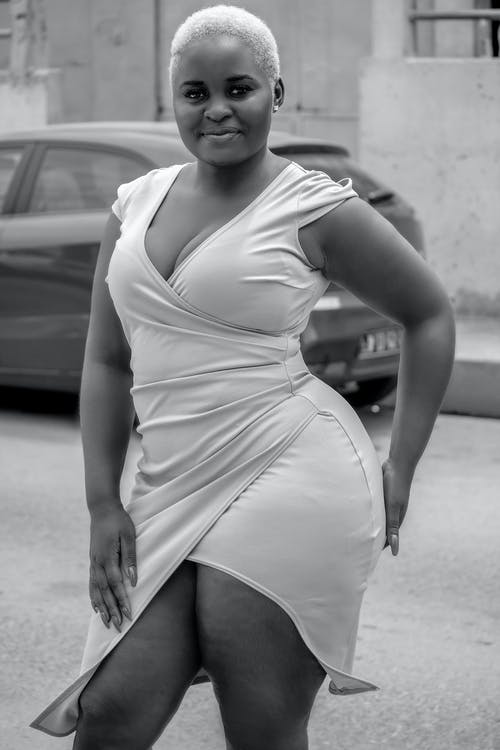 Black and white of plus size African American female with short hairstyle in dress looking at camera on street