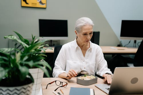 Elderly Woman Eating While Working