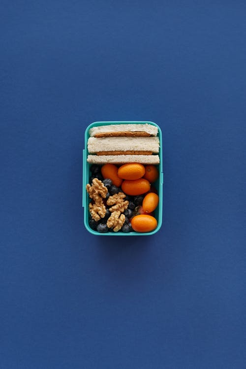 Brown and White Nuts in Blue Plastic Container