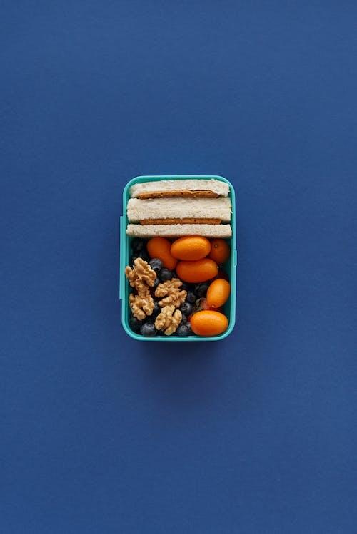 Braune Und Weiße Nüsse Im Blauen Plastikbehälter