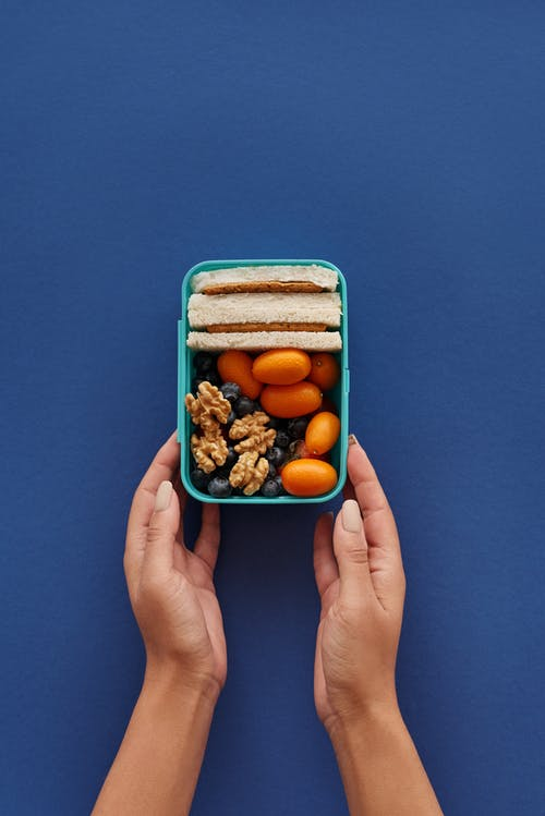 Person Holding Blue Plastic Container With Brown and White Food