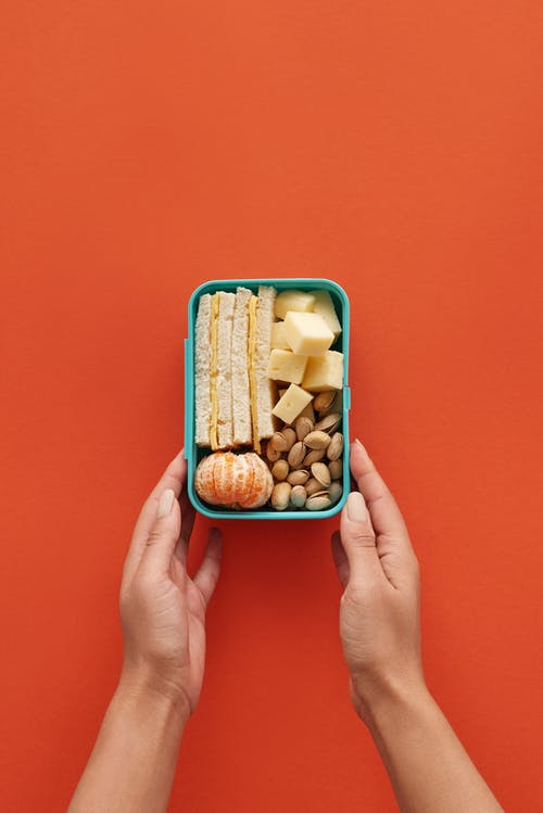 Person Holding Blue Plastic Container With Brown and White Beans