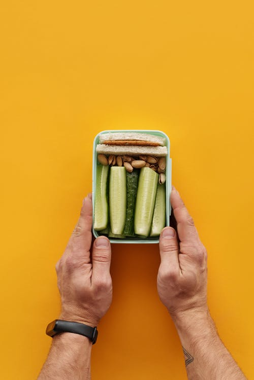 Person Holding Green and White Food