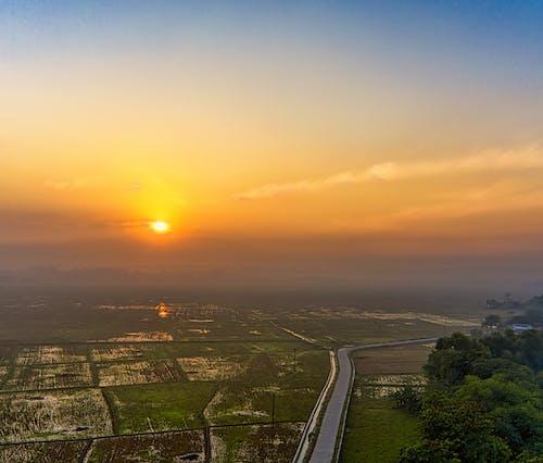Bright orange sunrise above green fields