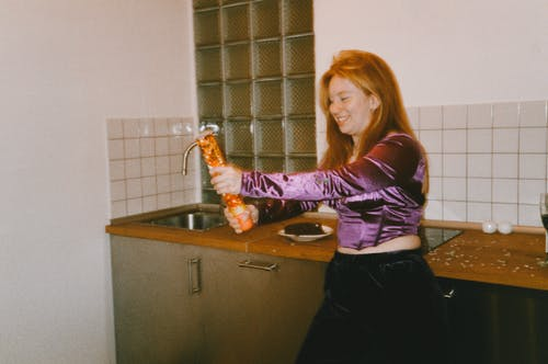 Woman in Purple and White Long Sleeve Shirt and Black Pants Standing in Front of Sink