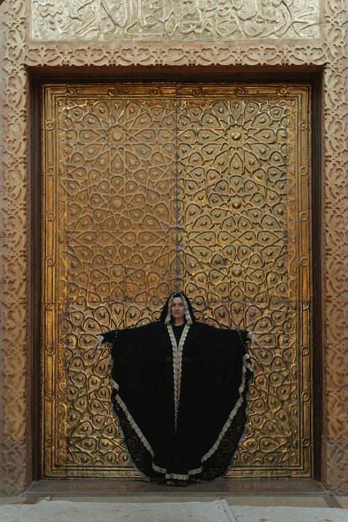 Woman In Black Abaya Standing Beside A Golden Door