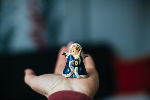 Person Holding White and Blue Ceramic Figurine