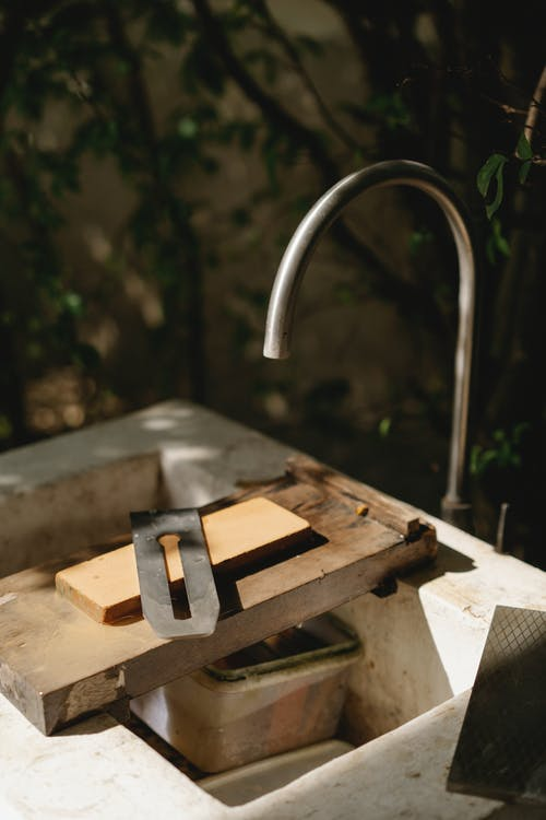 Old sink with tap and wooden blocks