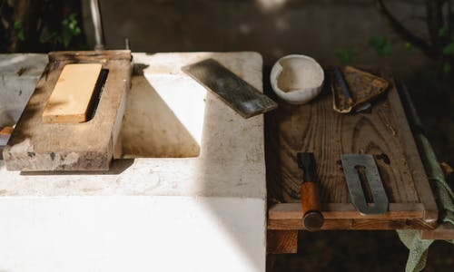 Assorted carpentry instruments on old washbasin outdoors