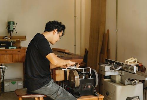 Outil D'affûtage Artisan Ethnique Attentif Sur Rectifieuse Dans L'atelier