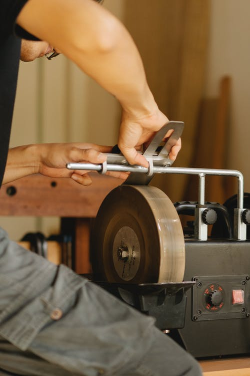 Crop craftsman sharpening tool on grinder in workshop