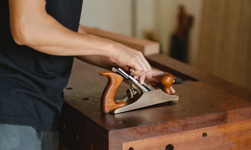 Side view of unrecognizable male carpenter changing knife in planer while cutting piece of board in studio on blurred background