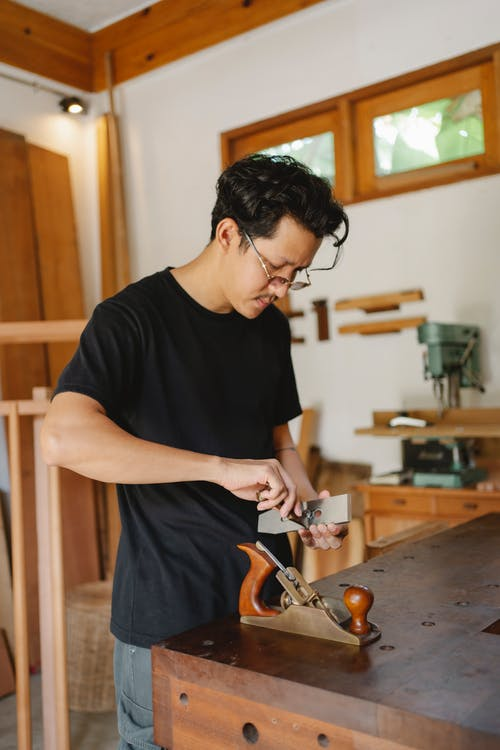 Concentrated male carpenter in eyeglasses standing with metal knife at wooden workbench with jointer during work process in joinery workshop