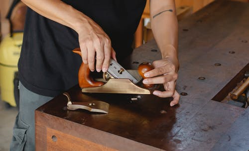 Anonymous male carpenter with tattoo adjusting knife in planer for cutting wood during work in professional workshop on blurred background