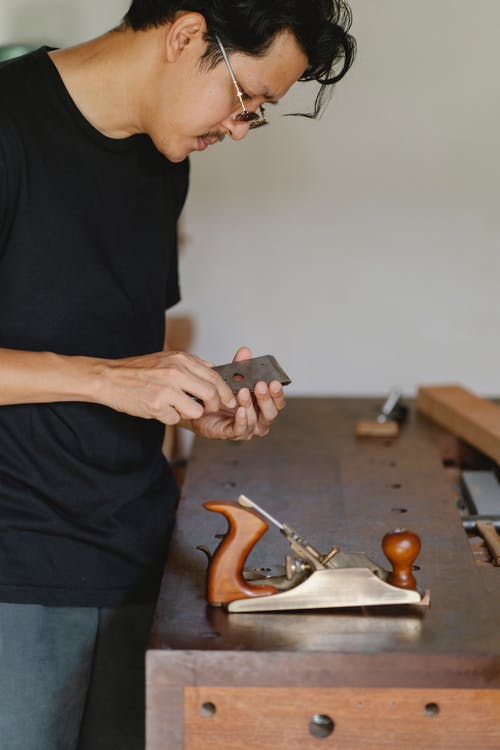 Side view of crop male master wearing eyeglasses with sharp knife from planer instrument for woodwork standing at table in workshop