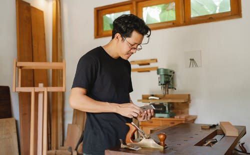 Focused artisan with special tool for woodwork