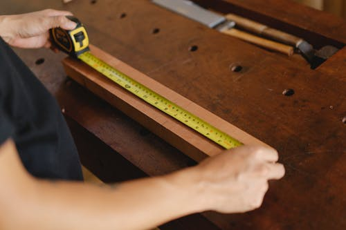 Unrecognizable male carpenter standing at wooden workbench and measuring length of board with yellow tape measure while working in professional studio