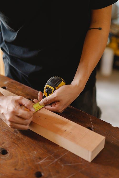 Crop artisan measuring width of plank