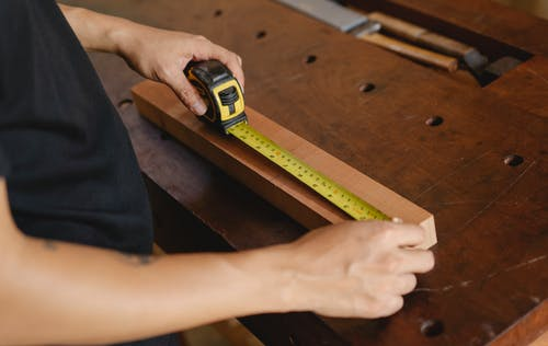 Precise unrecognizable male carpenter accurately measuring wooden detail while using ruler during work at workbench with instruments in professional studio