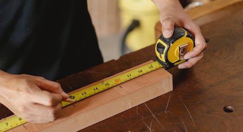 Crop man using ruler in workshop