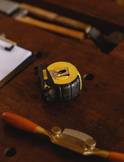 Special yellow ruler placed on wooden workbench near professional tools with joinery instruments for carpentry near clipboard in workshop on blurred background