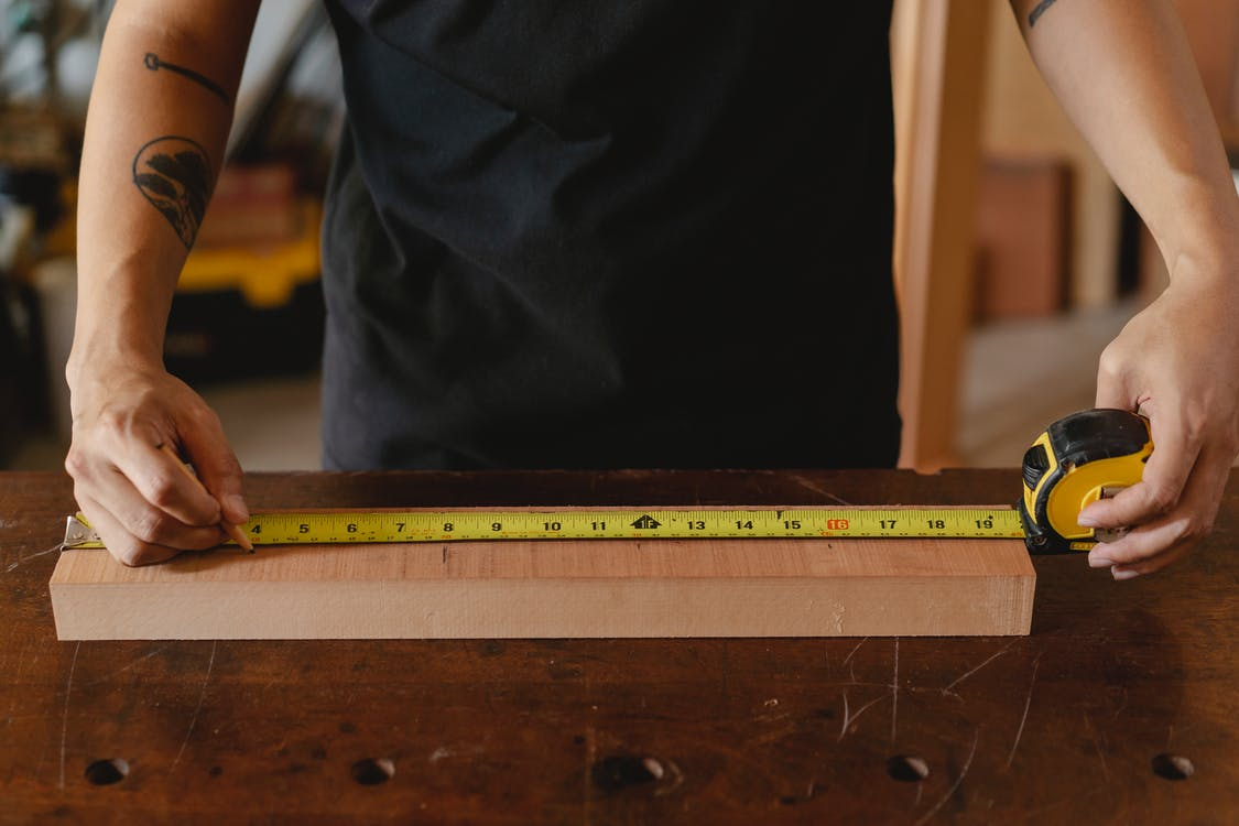 Unrecognizable male carpenter in black outfit with tattoo using ruler on wooden plank while working in studio on blurred background