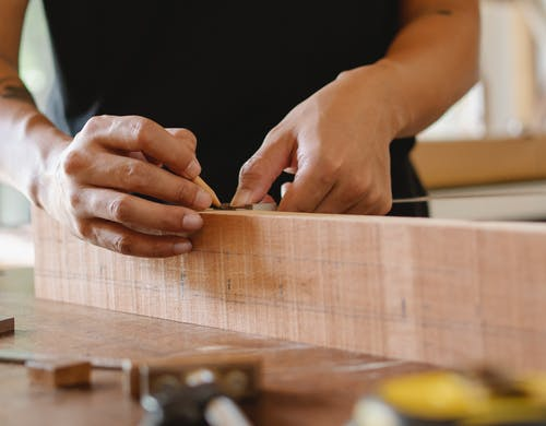 Unrecognizable male master using pencil and ruler to measure width of wooden detail while working in professional workshop on blurred background