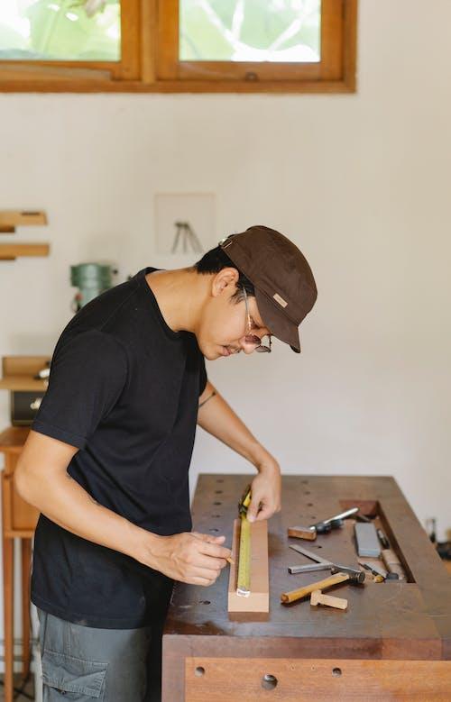 Carpinteiro étnico Medindo Prancha De Madeira Em Oficina