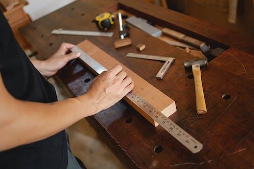 Человек, измеряющий деревянную доску с линейкой