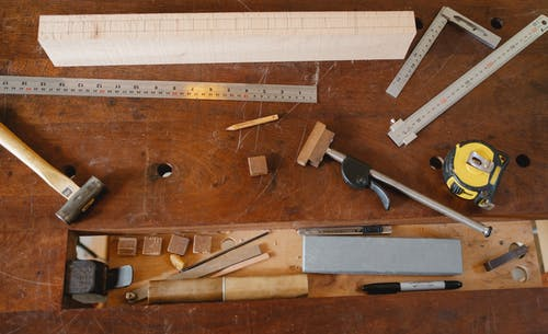 Top view of various equipment for joinery and measuring placed on timber table