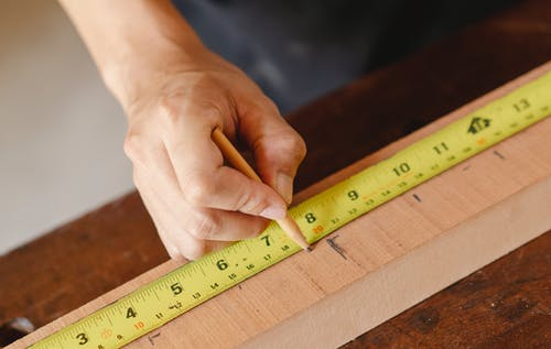 Man making marks on wooden plank with measurement tape