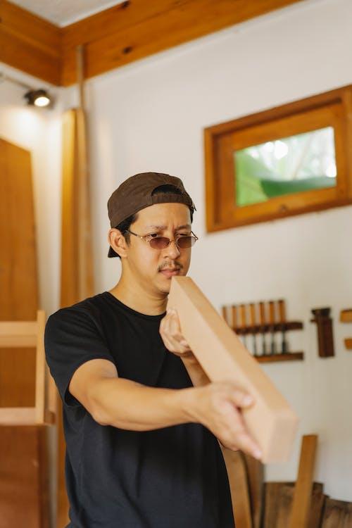 Erwachsener Asiatischer Mann In Brillen, Die Holzplanke Untersuchen