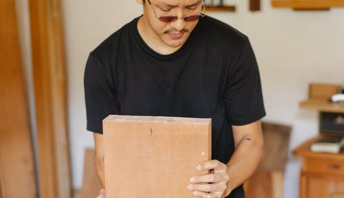 Crop ethnic focused male in eyeglasses and casual outfit doing carpentry on blurred background of workshop