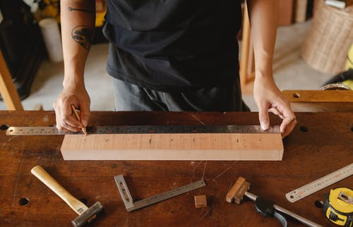 Man with tattoo measuring wooden plank with metal ruler