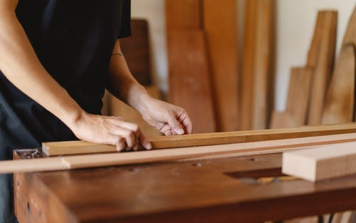 Experienced artisan doing woodwork on table in workshop