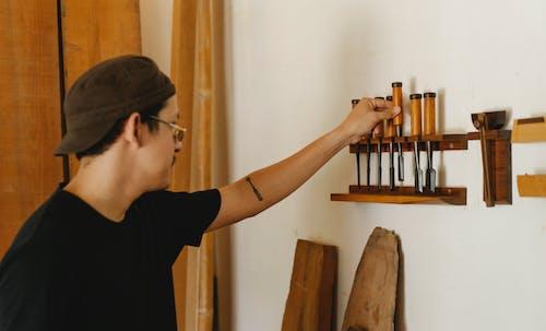 Serious man in eyeglasses choosing instruments for joinery