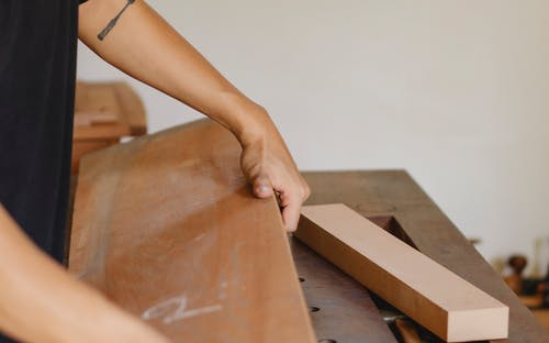 Man working with heavy wooden plank in joinery studio