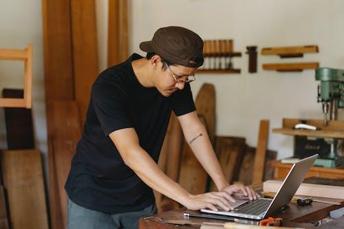 Focused man using laptop in workshop studio