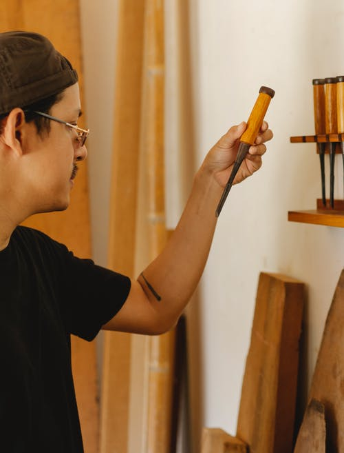 Side view of crop craftsman in casual clothes and eyeglasses choosing chisels for wood carving while working in studio in daytime