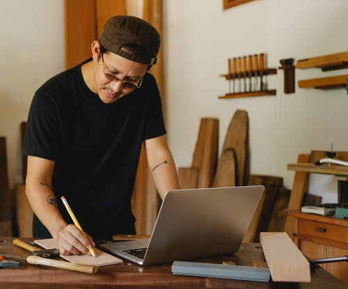 Concentrated ethnic craftsman using netbook and writing notes while working in creative workspace in daytime
