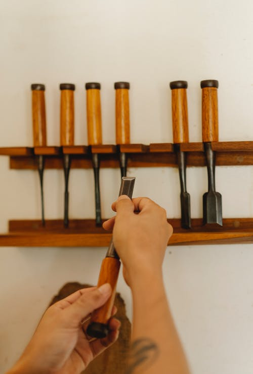 Person choosing chisels for wood carving