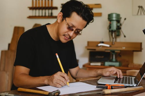 Concentrated ethnic craftsman with black hair and mustache in eyeglasses using laptop and taking notes on paper while working in professional carpenter studio