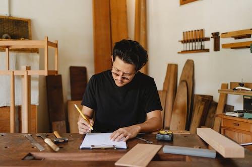 Focused ethnic craftsman working in creative carpenter studio