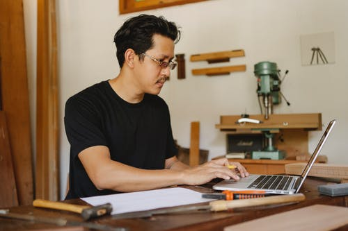 Concentrated Asian male in glasses sitting at table with various equipment and browsing netbook during work day